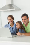 Portrait of a family using a laptop in the kitchen Stock Photo