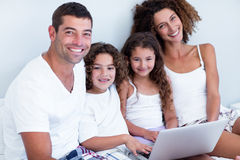 Portrait of family using laptop together on bed Stock Images
