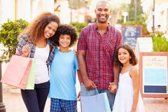 Portrait Of Family Walking Along Street With Shopping Bags royalty free stock photos