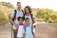 Portrait Of Family Wearing Backpacks Hiking In Countryside Together stock photography