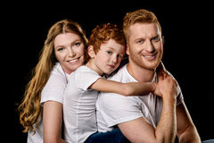 Portrait of family in white t-shirts hugging each other. Isolated on black royalty free stock images