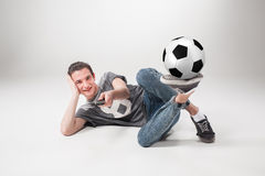The portrait of fan with ball, holding  tv remote on gray background Stock Images