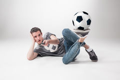 The portrait of fan with ball, holding  tv remote on white background Royalty Free Stock Photography