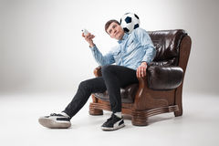 The portrait of fan with ball, holding  tv remote on white background Stock Image