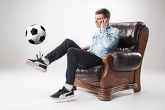 The portrait of fan with ball, holding  tv remote on white background Stock Photo