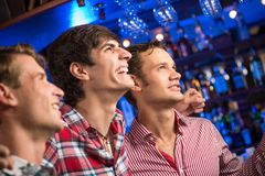 Portrait of the fans in the bar. Three men stand in a row embracing smile and look in front of you, sports fans Stock Images