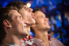 Portrait of the fans in the bar. Three men stand in a row embracing smile and look in front of you, sports fans Stock Image