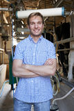 Portrait Of Farmer With Dairy Cattle In Milking Shed Royalty Free Stock Images