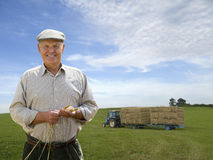 Portrait of farmer in field with wheat bales on tractor in background Royalty Free Stock Photo
