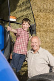 Portrait of farmer and grandson near tractor and hay Stock Photos