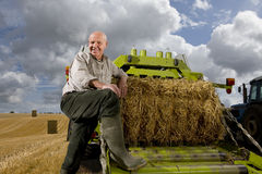 Portrait of farmer leaning on machinery with straw bale Royalty Free Stock Images