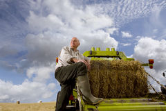 Portrait of farmer leaning on machinery with straw bale Stock Images
