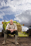 Portrait of farmer sitting on machinery with straw bale Royalty Free Stock Image