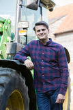 Portrait Of Farmer Standing Next To Tractor Stock Photography