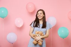 Portrait of fascinating joyful young woman in blue dress holding and hugging teddy bear plush toy on pink background. With colorful air balloons. Birthday stock photos