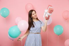 Portrait of fascinating woman in blue dress looking on red box with gift present holding colorful air balloons on pink. Trending background. Birthday holiday stock images