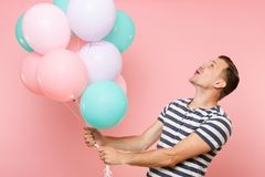 Portrait of fascinating young happy man wearing striped t-shirt holding colorful air balloons isolated on bright. Trending pink background. People sincere stock photos