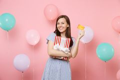 Portrait of fascinating young woman in blue dress holding credit card and red box with gift present on pastel pink. Background with colorful air balloon royalty free stock image