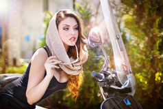 Portrait of fashion attractive girl with headscarf and sunglasses besides an old scooter Royalty Free Stock Photo
