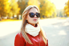 Portrait of fashion blonde woman wearing a sunglasses. And red leather jacket with scarf in autumn park Royalty Free Stock Images