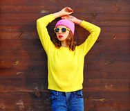 Portrait fashion cool girl in colorful clothes over wooden background wearing pink hat yellow sweater Stock Photos