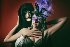 Portrait of a fashion couple with venetian masks Stock Photos