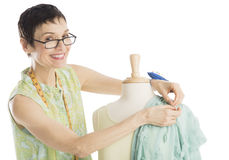 Portrait Of Fashion Designer Pinning Clothes To Mannequin. Portrait of happy female fashion designer pinning clothes to mannequin against white background royalty free stock photos