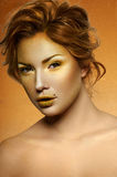 Portrait of fashion Female Model with golden Makeup Stock Images