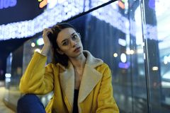 Portrait of fashion female model posing in yellow jacket and glasses, in city lights by night. Womenswear style royalty free stock photography