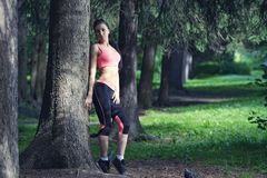Portrait of fashion fitness model posing in park Stock Photos