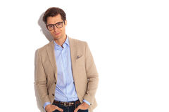 Portrait of fashion guy wearing glasses. Posing with both hands in pockets while smiling at the camera in isolated studio background Stock Photo