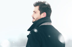 Portrait of fashion handsome man in winter snowstorm looks, profile view. Portrait of fashion handsome man in winter snowstorm looks into distance, profile view Royalty Free Stock Images