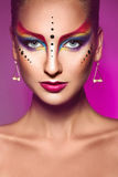 Portrait of fashion model with multicolor make up on purple back Royalty Free Stock Photo