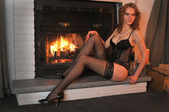 Portrait Fashion model posing in front fireplace Royalty Free Stock Photos