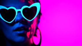 Portrait of fashion model woman with heart shaped glasses in neon light. Fluorescent unusual makeup glowing under UV stock video footage