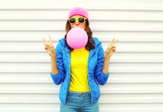 Portrait of fashion pretty cool girl blowing pink air balloon in colorful clothes having fun over white wearing a pink hat. Portrait of fashion pretty cool girl Stock Photography