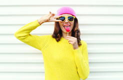 Portrait of fashion pretty cool girl with lollipop in colorful clothes over white background wearing a pink hat yellow sunglasses Stock Photography