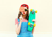 Portrait fashion pretty cool girl with lollipop and skateboard over white Royalty Free Stock Photo