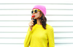 Portrait fashion pretty cool girl sucking lollipop in colorful clothes over white background wearing pink hat yellow sunglasses Royalty Free Stock Photos