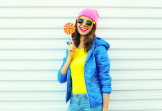 Portrait fashion pretty cool smiling woman with lollipop in colorful clothes over white background, wearing a pink hat Stock Image