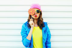 Portrait fashion pretty cool woman with lollipop in colorful clothes over white background wearing a pink hat yellow sunglasses Stock Photos