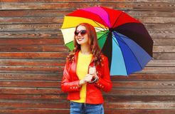 Portrait fashion pretty smiling woman with colorful umbrella in autumn over wooden background wearing red leather jacket Royalty Free Stock Image