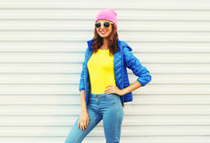 Portrait fashion pretty smiling woman model in colorful clothes posing over white background wearing a pink hat yellow sunglasses Stock Photos
