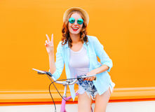 Portrait fashion pretty woman with bicycle on a colorful orange Stock Photography