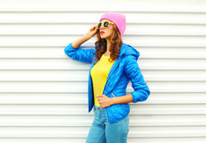 Portrait of fashion pretty woman model in colorful clothes posing over white background wearing a pink hat yellow sunglasses Stock Photos