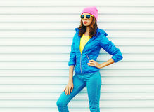 Portrait fashion pretty woman model in colorful clothes posing over white background wearing a pink hat yellow sunglasses Stock Photos