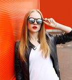 Portrait fashion pretty woman wearing a rock black leather jacket and sunglasses in city over red Royalty Free Stock Photography