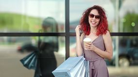 Portrait fashion redhead girl with shopping bag enjoying break drinking coffee paper cup outdoor. Medium shot. Smiling female in trendy sunglasses having fun stock video footage