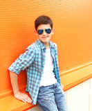 Portrait fashion smiling child boy wearing a sunglasses and shirt. In city stock photo