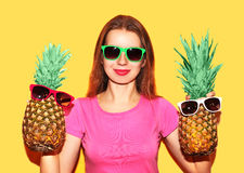 Portrait fashion smiling woman and two pineapple in sunglasses over yellow Stock Photography
